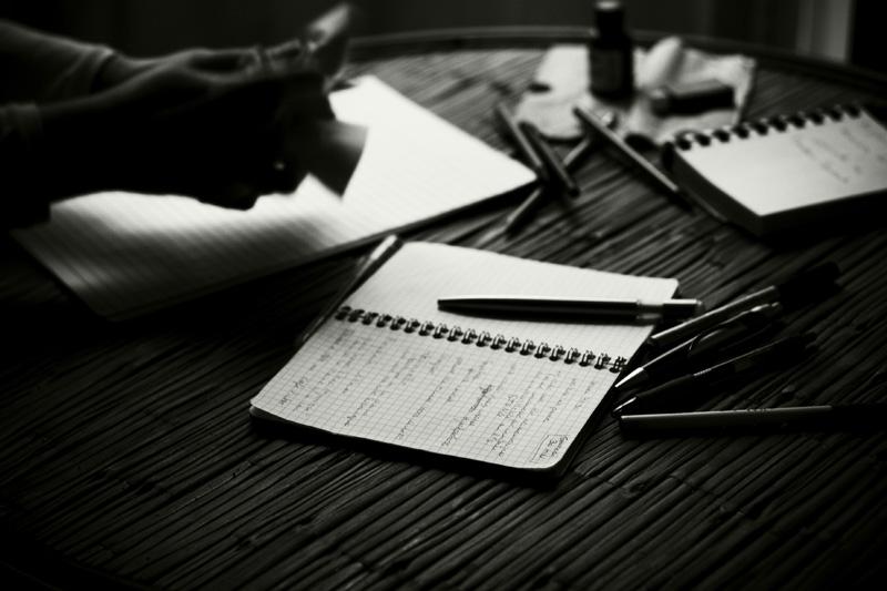 Photo noir et blanc de carnets et de stylos.